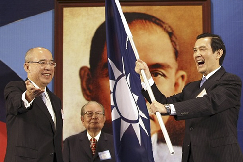 Taiwan President Ma waves the party flag as outgoing KMT Chairman Wu smiles during the KMT's national congress in Taipei